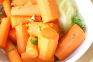 close up of cooked carrots and cabbage with parsley on top