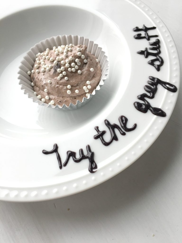 """Try the grey stuff"" written on a plate that's holding the grey stuff dessert"