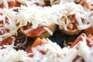 taco stuffed shells - covered in shredded cheese