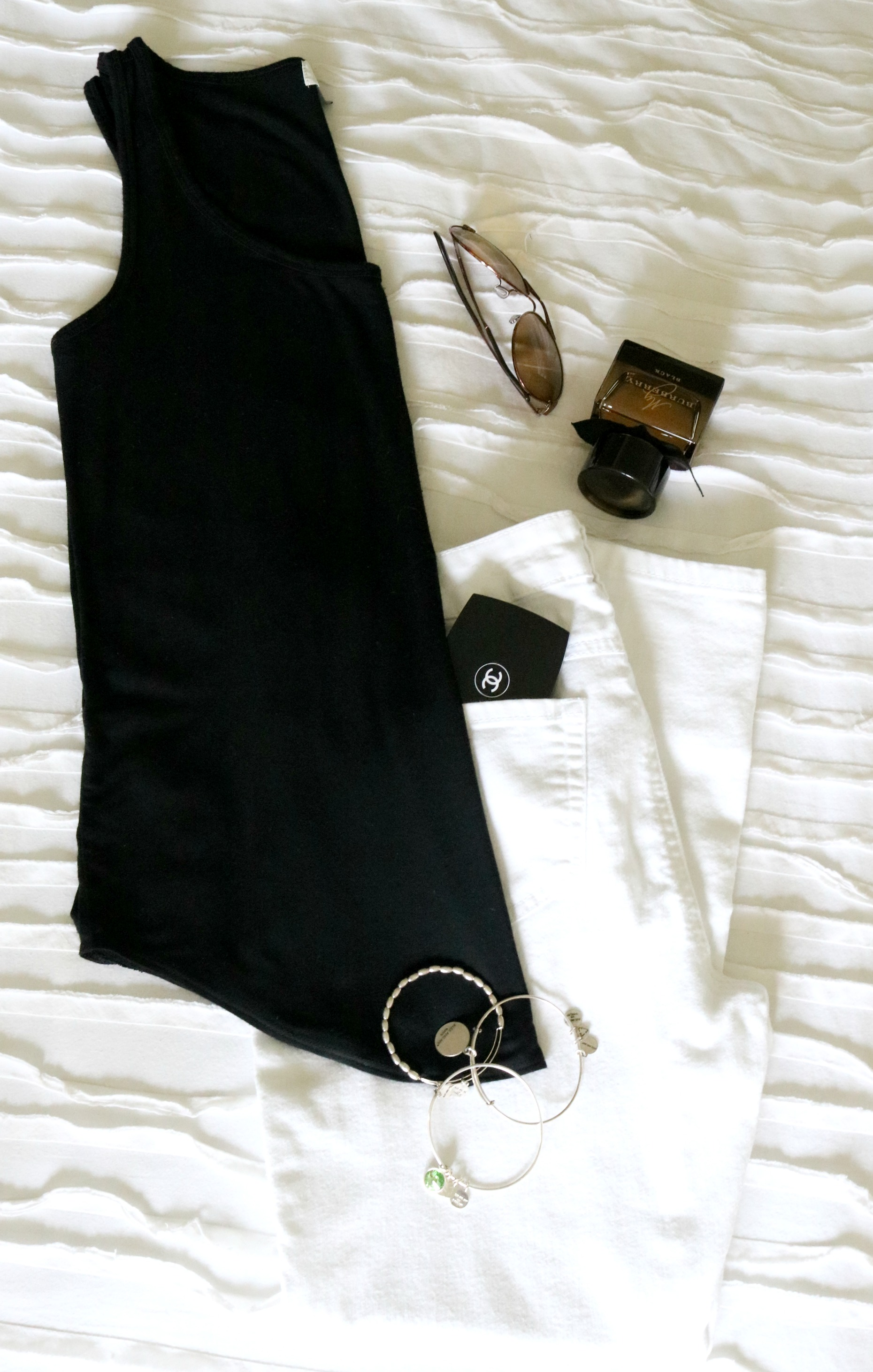flat lay of black tank, white jeans and accessories
